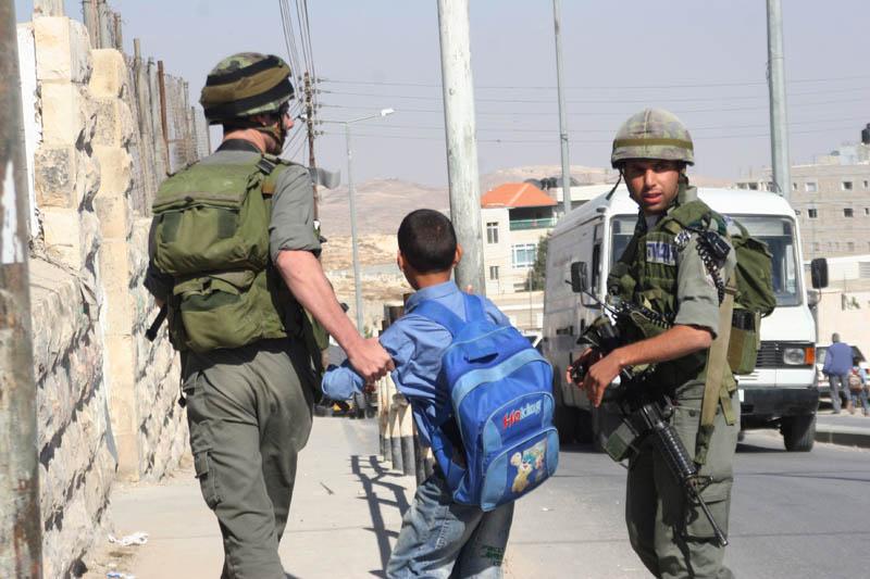 IDF soldiers arresting a Palestinian boy.