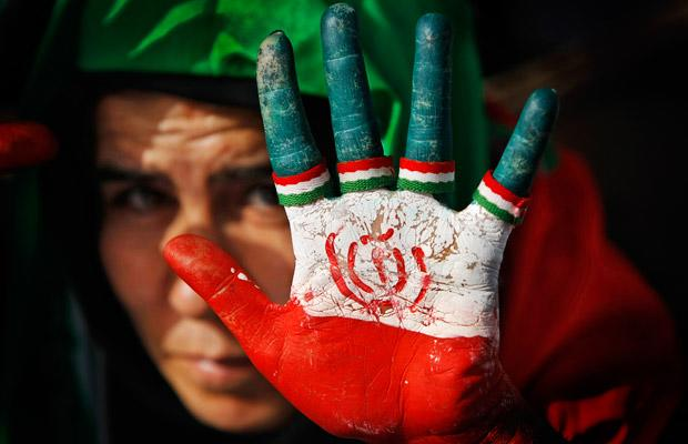 A female supporter of Iranian President Mahmoud Ahmadinejad displays her hand painted with the Iranian flag, also used as a sign for his party (Photo: AP)