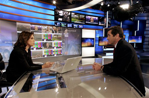 "CNN's Soledad O'Brien, left, and Miles O'Brien rehearse with the network's ""news wall"" in the background."