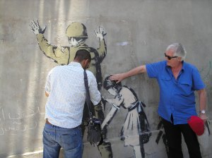 Henning Mankell (right) responds to Banksy's wall art