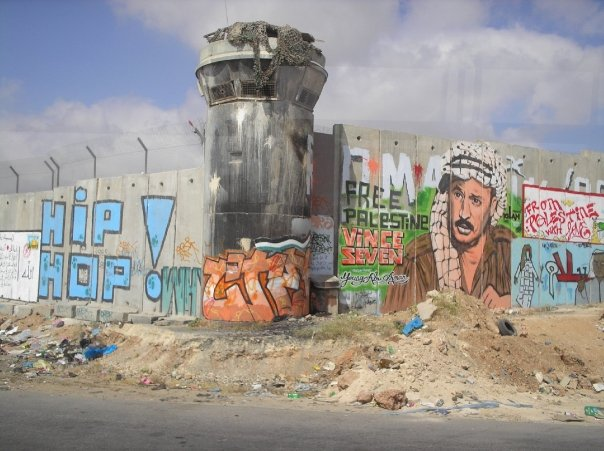 At the Qalandia checkpoint separating Ramallah from Jerusalem. Leila Khaled's head peeks out between the I and O of Hip Hop.