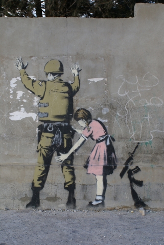 Some graffiti by Banksy in Bethlehem: A Palestinian girl frisks a soldier.