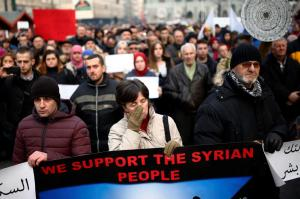 """A woman, holding a placard reading """"We support the Syrian people"""", cries as she stands among other Bosnians during a protest in Sarajevo"""